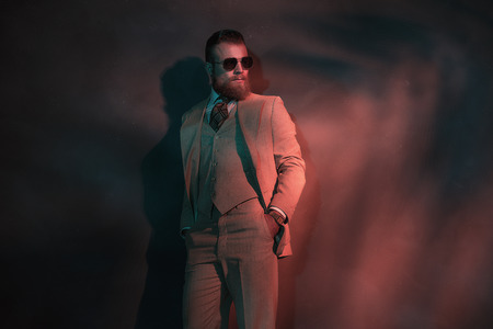 dapper: Stylish trendy man in a three piece elegant cream suit standing leaning against a wall in a nightclub with red lighting looking off to the right, with copyspace