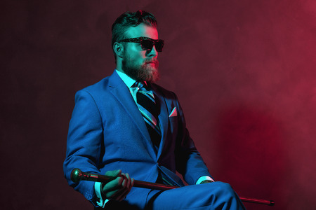 composure: Stylish bearded gentleman with a cane and sunglasses sitting in room with red toned lighting looking off to the right of the frame with a serious expression Stock Photo
