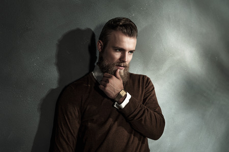 upper body: Thoughtful worried bearded young man with his hand to his chin standing staring at the floor, upper body portrait
