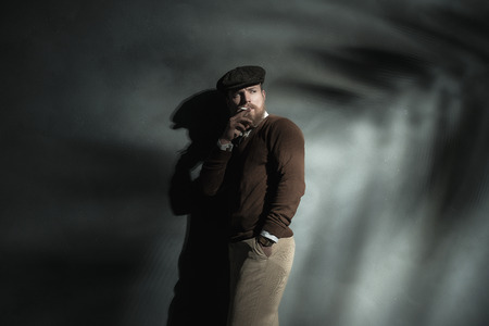 back cloth: Trendy man in a brown cloth cap leaning against a grey wall with his back to a beam of light smoking a cigarette, with copyspace