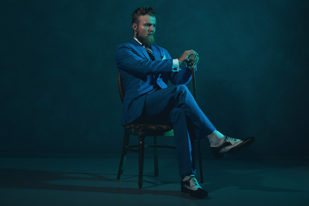 dashing: Elegant retro style gentleman with a cane sitting in a chair looking thoughtfully off to the side in a blue toned dark environment with copyspace Stock Photo
