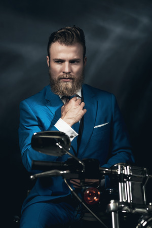 introspective: Handsome bearded businessman in a blue suit sitting waiting on a motorbike in the darkness looking thoughtfully, with copyspace Stock Photo