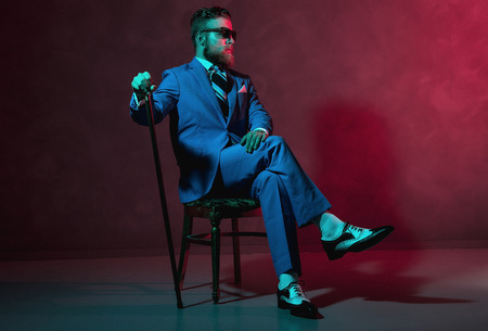 dapper: Handsome trendy old-fashioned dandy with a beard and sunglasses sitting in a chair holding his cane, red toned lighting in darkness with copyspace Stock Photo