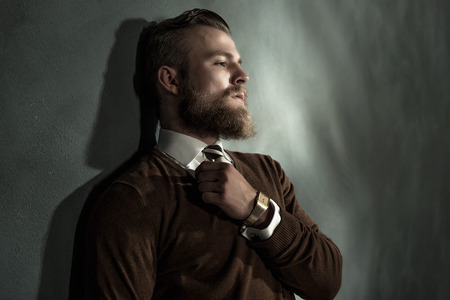 introspective: Thoughtful handsome bearded man standing daydreaming with his eyes closed and gripping his necktie, head and shoulders profile view