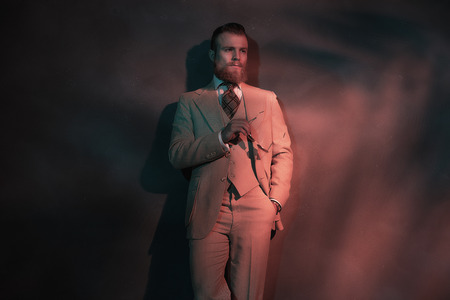 nonchalant: Handsome sexy bearded man in a stylish suit standing leaning against a wall in red toned atmospheric lighting, with copyspace