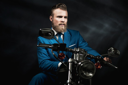 reverie: Handsome bearded businessman in a blue suit sitting waiting on a motorbike in the darkness looking thoughtfully off to the side, with copyspace