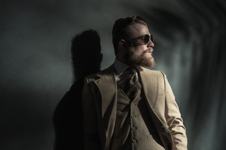 nonchalant: Stylish handsome bearded young man in a three piece cream suit standing leaning back against a grey wall looking off to the side