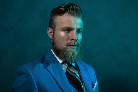 impassive: Portrait of a handsome thoughtful bearded young man in a suit looking down towards the ground with a pensive expression, head and shoulders on dark background