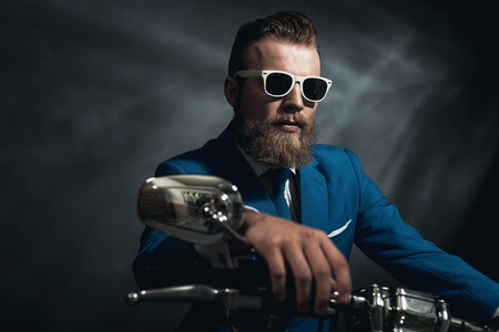 Stylish trendy man wearing modern sunglasses and a formal suit sitting waiting on a motorcycle, frontal view