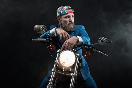 reversed: Hip businessman wearing a reversed baseball cap sitting waiting on his motorbike with a glowing headlight looking off to the side in the shadows Stock Photo