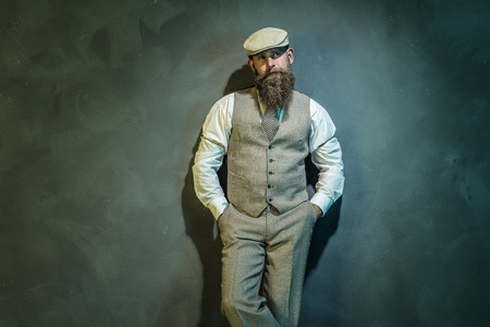 three quarter: Three quarter Shot of an Elegant Middle Aged Bearded Man with Hat Leaning Against the Wall with Hands in the Pockets and Looking Into the Distance.