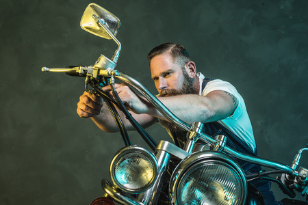 olden day: Handsome Bearded Man Repairing his Vintage Motorcycle Seriously Against Black Smoky Wall Background. Stock Photo