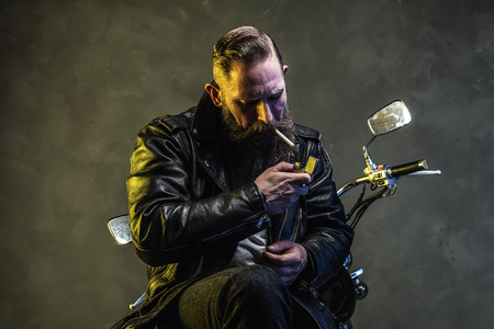 lighting background: Stylish Bearded Man in Black Leather Jacket and Jeans Lighting a Cigarette While Sitting on his Motorcycle Against Smoky Background.