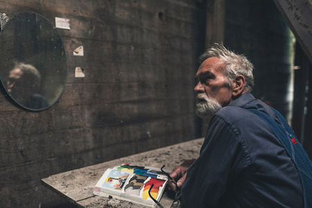 Thoughtful Senior Bearded Man Sitting Inside the Farmhouse with Magazine on the Table, Looking Into the Distance Seriously.