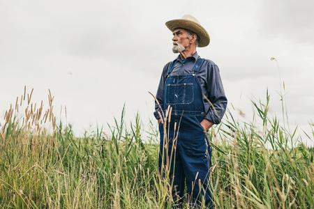 シニア髭麦わら農場で立っている兼業農家男性と距離を真剣に検討します。