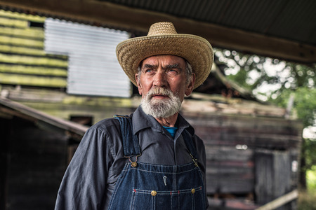 Old farmer standing in front of a rustic dilapidated wooden barn staring thoughtfully off to the side