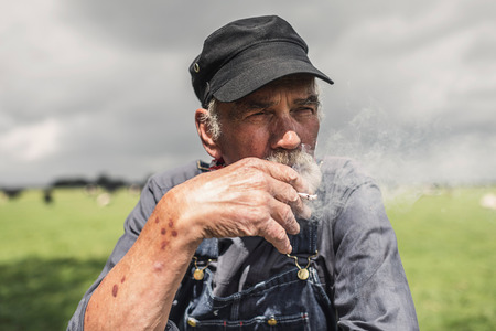 grizzled: Elderly grizzled farmer enjoying a smoke break standing smoking a cigarette outdoors in his fields and staring off into the distance with a serious expression