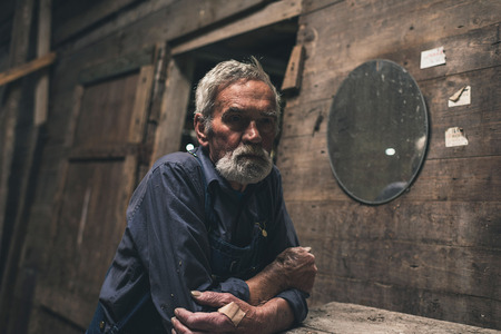 alone person: Lonely farmer sitting inside an old rustic wooden barn or house at an old weathered table with a thoughtful expression Stock Photo