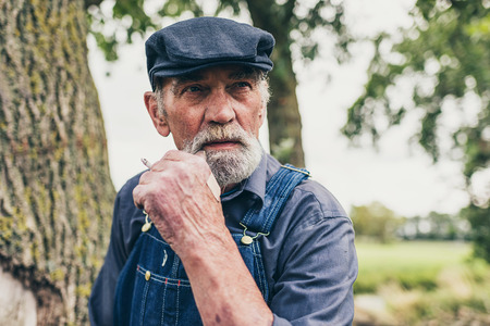 senior smoking: Senior grey-haired bearded country farmer standing smoking in his cloth cap and denim dungarees as he stares thoughtfully into the distance