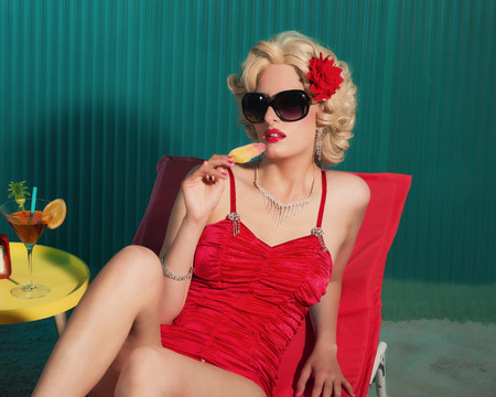 sensuous: Elegant Blond Woman in Red Fashion with Sunglasses, Holding an Ice Pop While Resting on a Beach Lounge Chair. Stock Photo