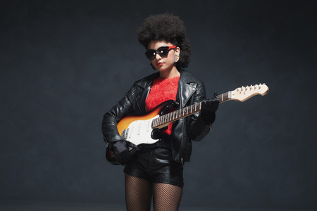 rocker girl: Three Quarter Shot of a Stylish Rocker Girl with Afro Hairstyle, Holding a Guitar Against Black Background