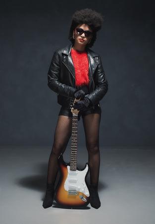 rocker girl: Tiro integral de una moda eje de balancín de la muchacha del afroamericano con el fondo de la guitarra baja contra la pared Negro.