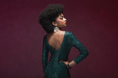 purple dress: Rear View of a stylish young African American woman in an elegant green evening dress against maroon background. Stock Photo