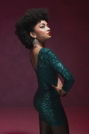 glamour woman: Rear View of a stylish young African American woman in an elegant green evening dress against maroon background. Stock Photo