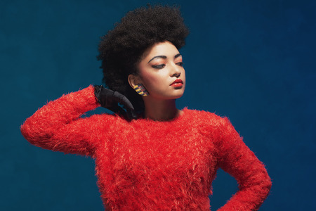eyes downcast: Close up elegant young woman with Afro hairstyle, wearing fashionable fuzzy tops, looking to the right frame with hand on her hair. Isolated on blue background.