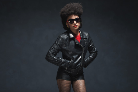 chic woman: Three Quarter Shot of a Fashionable Young Woman with Afro Hairstyle, Wearing Leather Jacket and Shorts with Sunglasses Against Black Background. Stock Photo