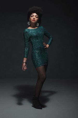 evening wear: Full Length Shot of a Young African American Woman Posing in an Elegant Sparkling Green Dress Against Black Background Inside a Studio. Stock Photo