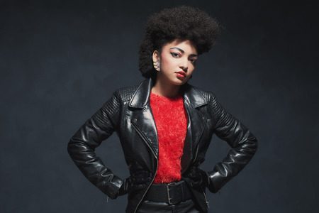 stylish woman: Half Body Shot of a Stylish Young African American Woman in Leather Jacket, Looking at the Camera Against Black Background. Stock Photo
