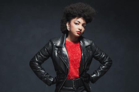 mujeres negras: La mitad Shot cuerpo de un elegante joven mujer afroamericana en la chaqueta de cuero, mirando a la cámara contra el fondo Negro.