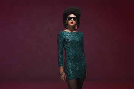evening wear: Three-quarter shot of a classy young woman wearing green dress with sunglasses in retro style, isolated on a purple background. Stock Photo