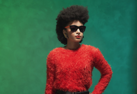 half body: half body shot of a stylish young woman in fuzzy red tops with sunglasses, looking into the distance against green wall background.