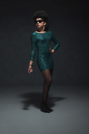 evening wear: Full Length Shot of a Young Woman with Afro Hairstyle, Posing in an Elegant Green Dress with Sunglasses Against Black Wall Background.
