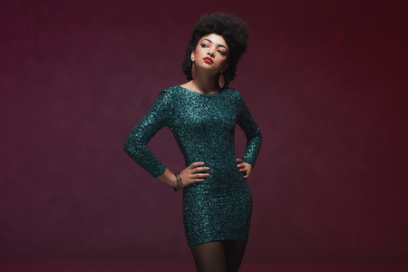 evening wear: Three-quarter shot of an elegant young woman, in a glittery green dress, looking at the camera. Isolated on maroon background. Stock Photo