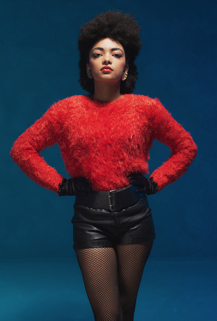 woman fashion: Three-quarter shot of a young woman with Afro hairstyle, wearing trendy furry red shirt and black leather shorts, looking at the camera against blue wall background. Stock Photo