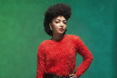 half body: Half body Shot of a Stylish Young Woman with Afro Hair, Wearing Furry Red Shirt and Black Shorts, Looking at the Camera Against Green Wall Stock Photo
