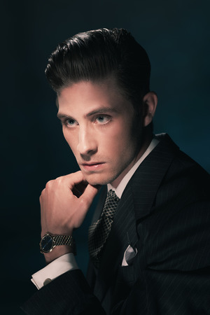 combed: Retro fashion man in suit and tie holding his chin. Hair combed back. Dark blue background. Studio shot. Stock Photo