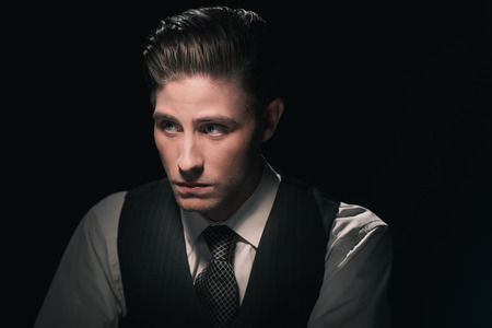 Retro 1940s fashion man in waistcoast and tie. Grease hair combed back. Against dark background.