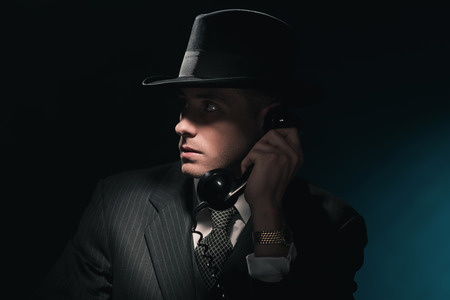 detective: Vintage young detective on the phone with hat in suit and tie. Dark blue background.