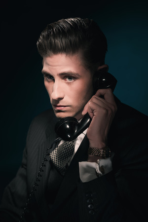 hair tie: Classic vintage businessman in suit and tie on the phone. Hair combed back. Against dark blue wall.