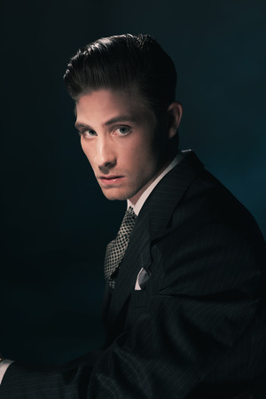 Classic stylish vintage man in suit and tie. Hair combed back. Dark blue background. Studio shot. Stock Photo