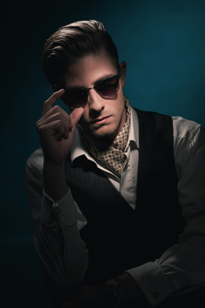 Handsome retro fashion man with vintage shades in waistcoat and scarf. Slick hair combed back. Against Dark blue background. Stock Photo