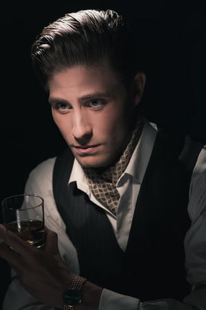 greasy: Retro fashion young man with glass of whiskey in waistcoat. Greasy Hair combed back. Dark blue background.