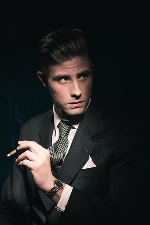 Cigar smoking retro 40s businessman in suit and tie. Hair combed back. Against dark background. Stockfoto