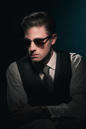 greasy: Classic stylish fashion man with sunglasses in waistcoat and tie. Greasy hair combed back. Against dark blue background. Stock Photo