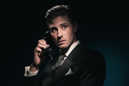 combed: Classic vintage businessman in suit and tie on the phone. Hair combed back. Against dark blue wall.