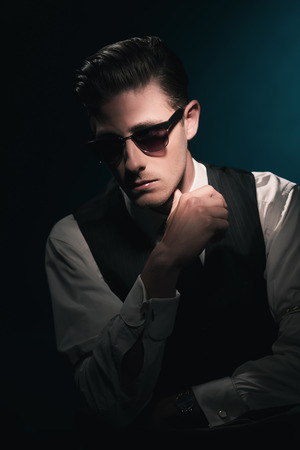 combed: Classic stylish fashion man with sunglasses in waistcoat and tie. Greasy hair combed back. Against dark blue background. Stock Photo